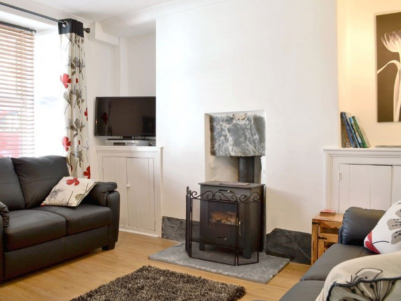 The living room and wood burning stove at Aspen Cottage in Windermere