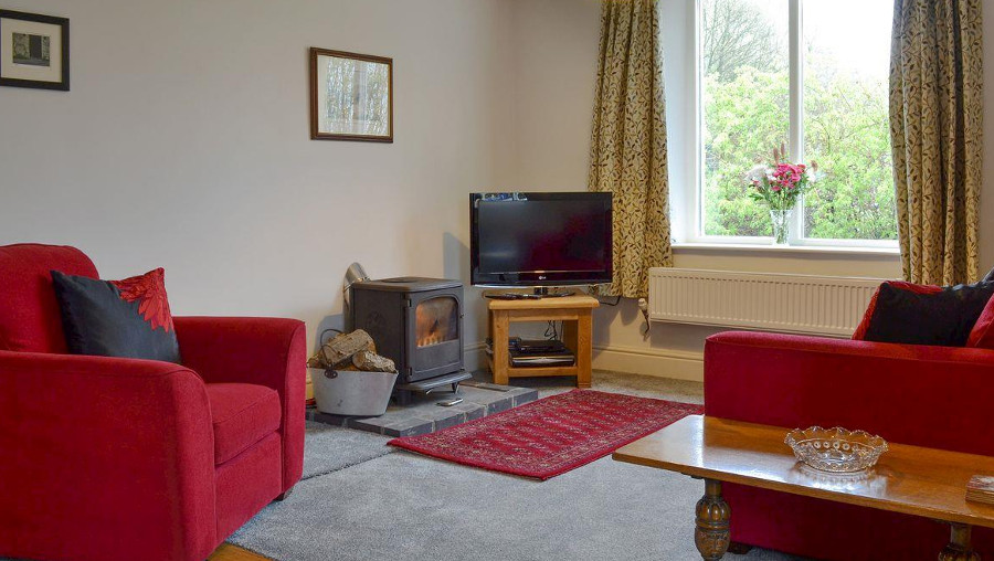 The living room with a wood burning stove at Bush Green Cottage in Cumbria