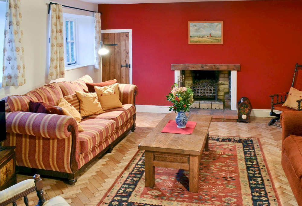 The living room and wood burning stove at Dyes Cottage near Holt