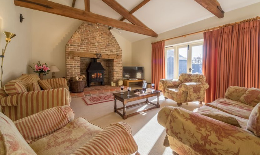 The living room at Geddings Farm Barn has a wood burning stove