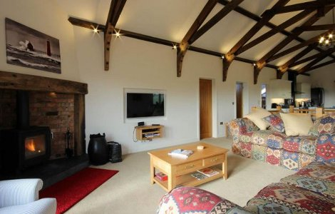 The living room, with wood burning stove, at Higher Hill Barn