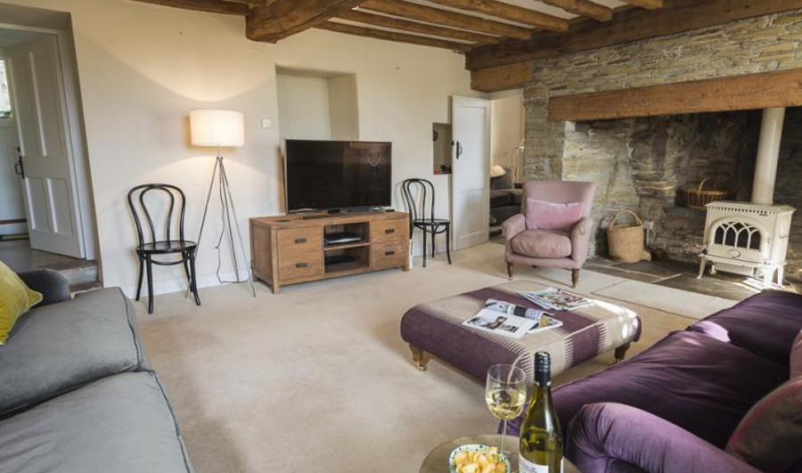 The living room with a wood burning stove at Lower Easton Farmhouse in Salcombe