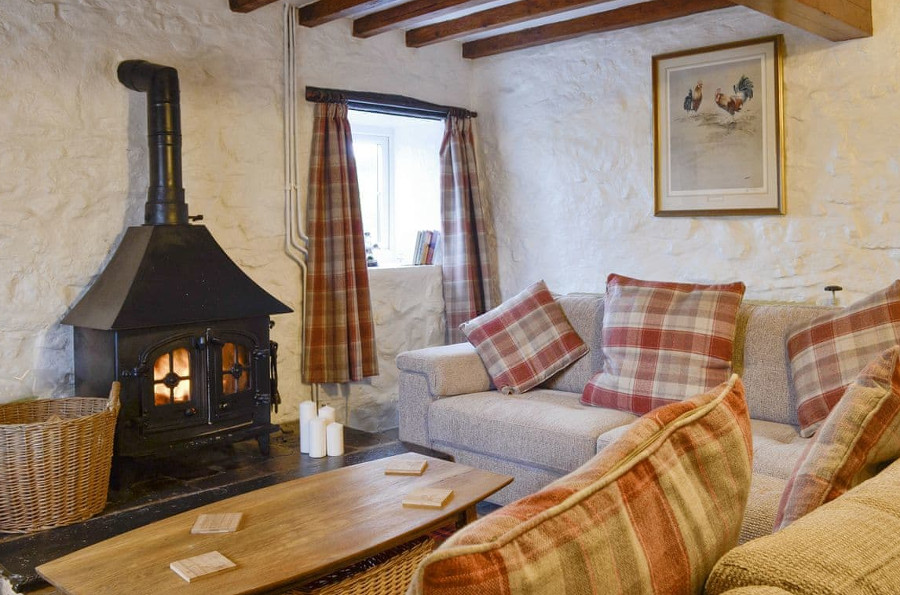 The living room with its wood burning stove at Wren Cottage near Prestatyn