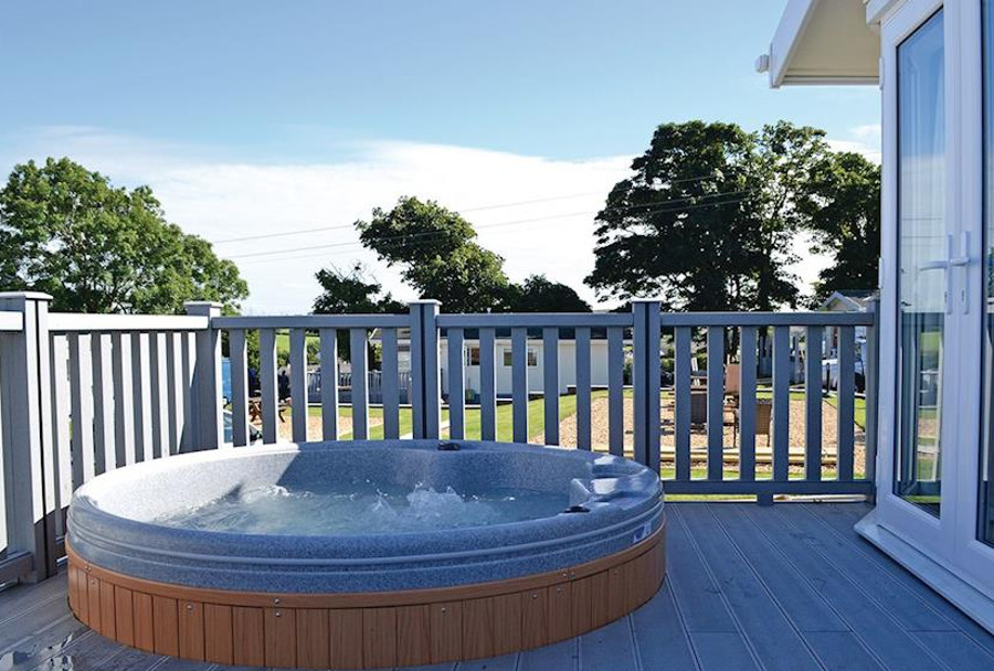 The outdoor hot tub at Woodpecker Lodge, Bryn Mechell Lodges