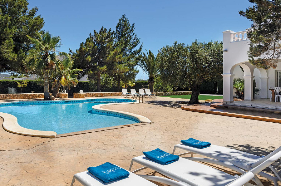 The swimming pool and sun loungers at Villa Oasis, Ibiza